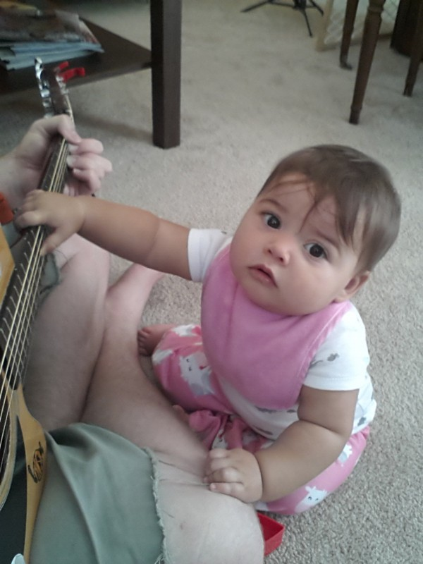 Helping Daddy play some guitar